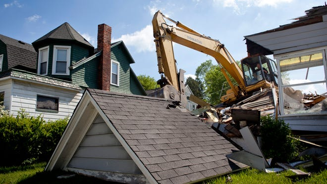 Crews demolish a home at 2204 Stone St. Wednesday, May 27, 2015 as part of a $1 million state grant the city received from the Michigan State Housing Development Authority to fight blight.