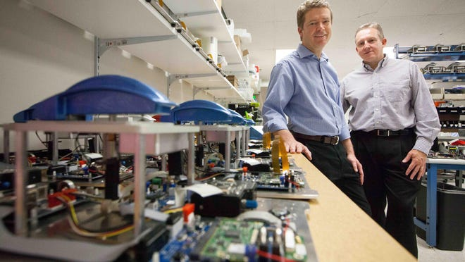 Denovix Managing Director Fred Keilhorn (left) and business director Kevin Kelley stand next to a line of spectrophotometers the company makes at their lab in Wilmington.