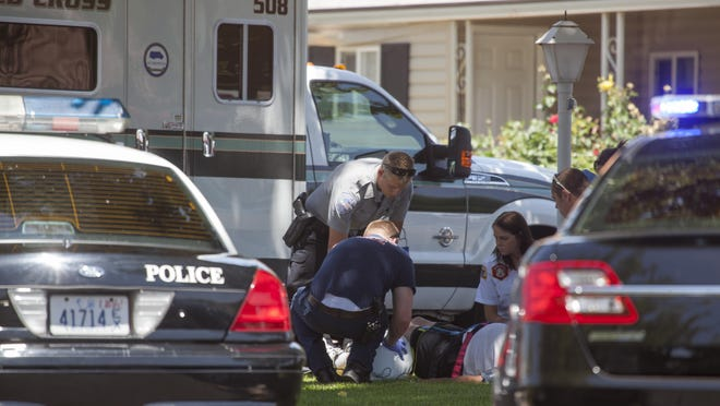 The Washington City Police Department and other first responders attend to a man injured while helping move a car which fell on a woman at Kings Row Estates Wednesday, June 3, 2015.