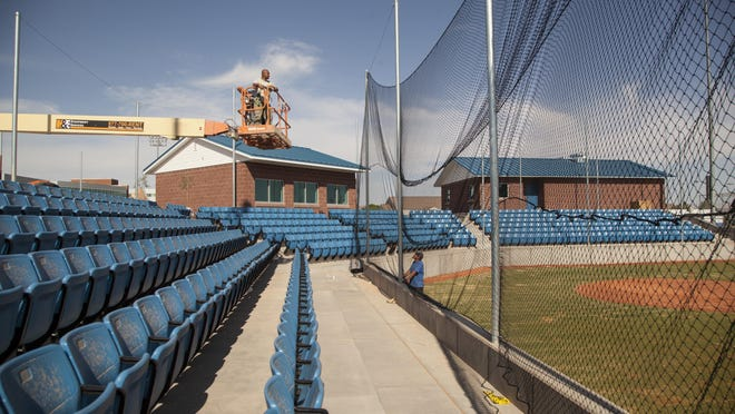 Workers hang netting at the new Dixie High School stadium Wednesday, June 3, 2015.