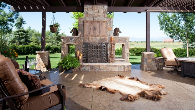 A covered grilling station, seating area and dining table/fire pit make up this Loveland outdoor living space with stained concrete patio.