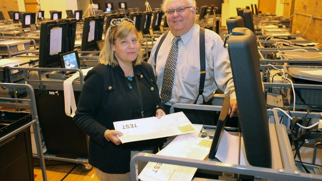 Rockland County Election Commissioners Kristen Zebrowski Stavisky and Louis Babcock stand among dozens of voting machines being prepped at the Dr. Robert L. Yeager Health Center campus in Ramapo in 2014.