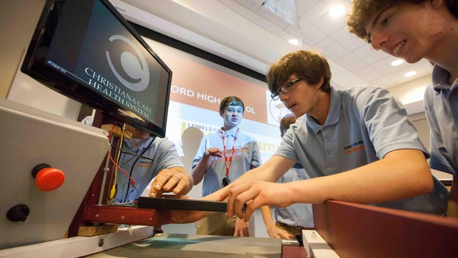 Matias Saavedra Silva, right, 16, and Dylan McAllister, 17, check on their machine as a team of students from Concord High School create a machine called S.H.A.R.P. that helps detect hazardous items, like scalpels and needles, to protect laundry workers at Christiana Hospital.