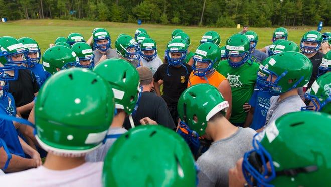 The Colchester High School football team huddles during Day 1 of high school football preseason practices.