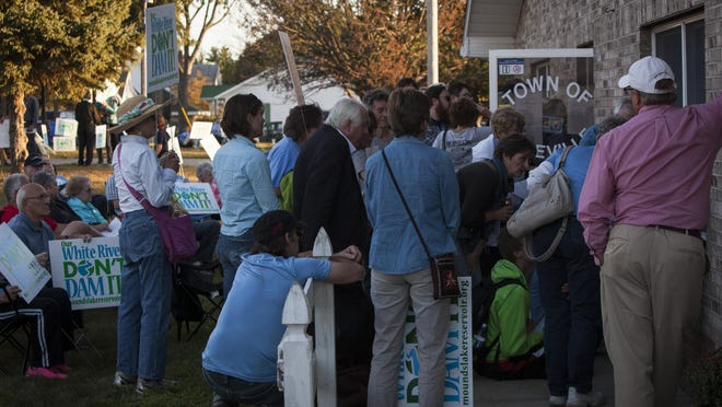 Members of the a large crowd opposing Mounds Lake wait on the lawn and listen by the windows of Daleville's Town Hall Monday evening during the vote for Mounds Lake. The Mounds Lake proposal was killed with all five council members voting no to it's adoption.