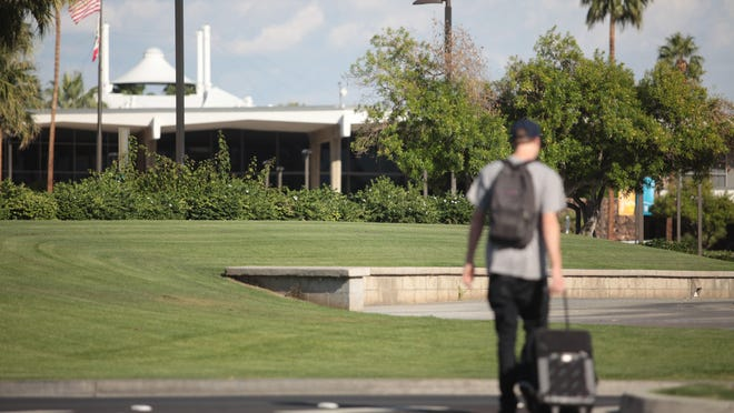 A traveler on Thursday walked past the lush lawn on the way to the Palm Springs International Airport terminal.
