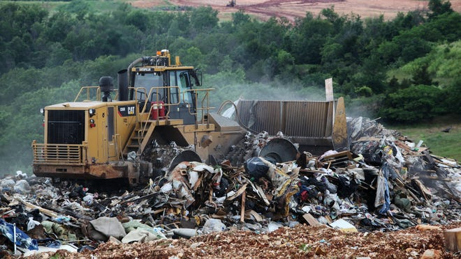 A worker compacts trash at the Springfield Sanitary Landfill on Friday, June 7, 2013.