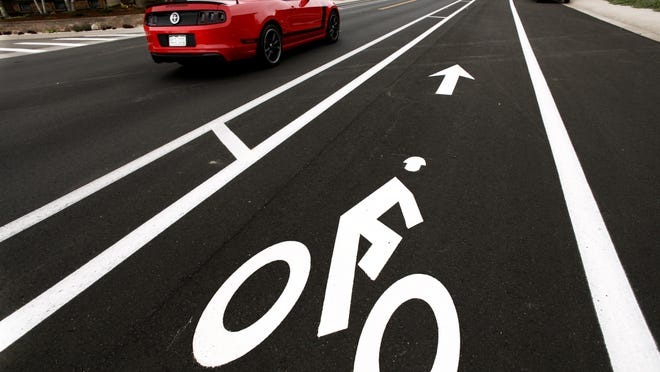 A buffered bike lane with a 3-foot section of striped lines on Lochwood Drive Monday, July 28, 2014. With a goal to make cyclist feel more comfortable and motorists more aware, the city is repaving streets and adding protective bike lanes in some locations.