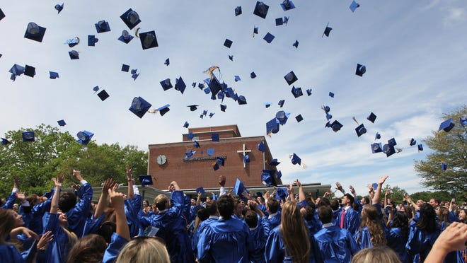 Our Lady of Lourdes High School graduates carry on with the tradition of the mortar board toss outside the school at the conclusion of the commencement ceremony.