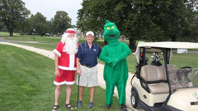 Holiday Express founder Tim McLoone in the middle with Santa and the Grinch.