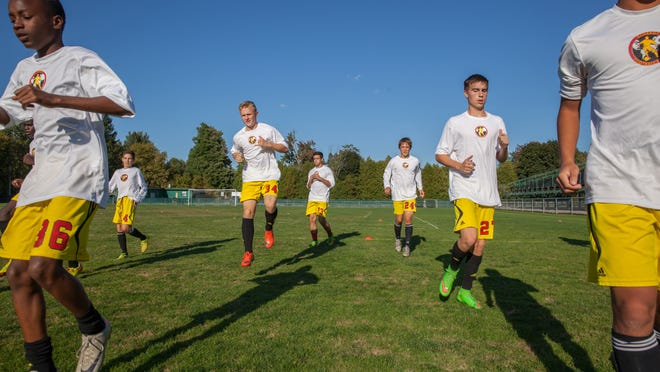 The Synergy soccer club runs through a drill during a recent practice at Centennial Field. Synergy switched to a 10-month season in August, a decision some high school coaches have questioned.