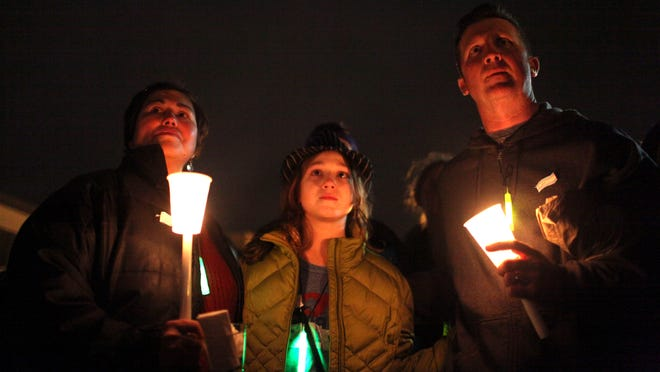 "Zay Crawford (center), a 12-year-old transgender girl from Yellow Springs, holds hands with her mother, Chasilee (left), and father, Jason (right) at a candlelight vigil to remember the life of Leelah Alcorn, a 17 year-old transgender girl, who committed suicide last month, in Kings Mills, Ohio. Saturday, January 3, 2015. Zay's grandparents and brother also attended the event to support. Chasilee said, ""We are a family. We love her for who she is and for what she is."""