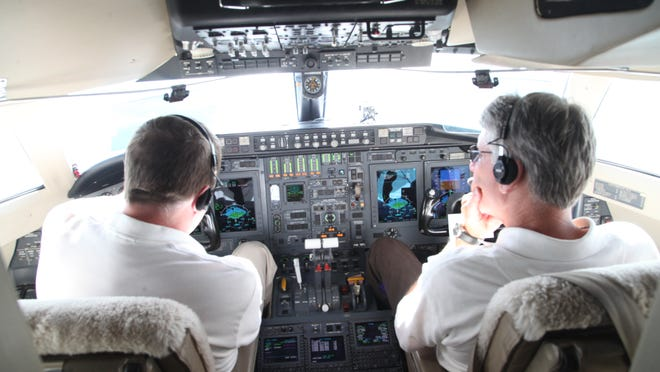 Rockwell Collins pilots Keith Kankelfitz, left, and Tom Yerke sit in the cockpit of a Bombardier Challenger 601 on Wednesday on a flight to demonstrate the company's new weather radar.