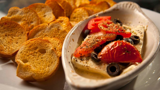 The Mediterranean baked cheese at Simon's includes salty feta, tomatoes and black olives baked in a ramekin until soft enough to spread on toast.