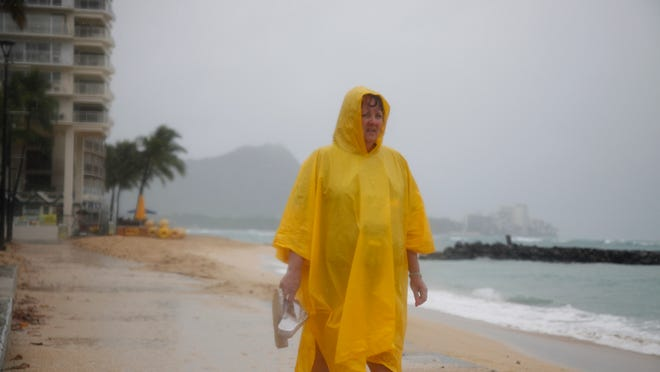 Maryanne Fisher, of League City, Texas, stands in the rain on Waikiki Beach with Diamond Head in the background in Honolulu Sunday, Oct. 19, 2014.