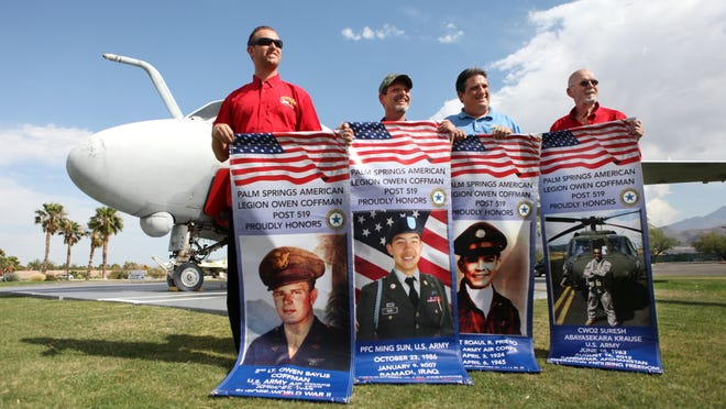 Tommy Winters, Lee Wilson, Fred Bell and Gary Black hold up banners honoring veterans at the Palm Springs Air Museum for the Freedom Flags for Families Initiative in May.