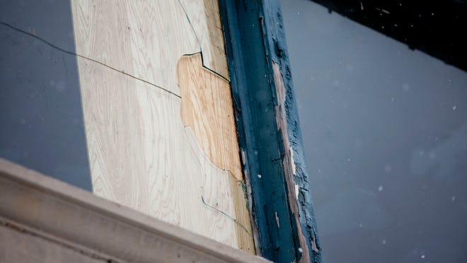 A broken window is covered with a board at the Sperry's Building in downtown Port Huron.