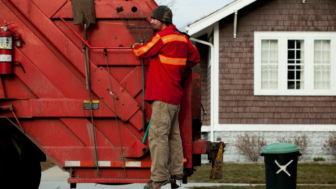 Marcotte Disposal workers collect garbage from the curb in Port Huron.