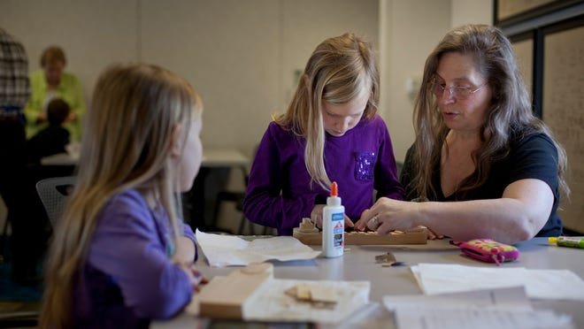 Candi Firmingham, of North Branch, helps her granddaughter Karlee Haack, 7, build a model boat as Haylee Haack, 8, left, watches at the Great Lakes Maritime Center in Port Huron.
