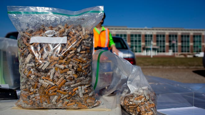 Thousands of cigarette butts picked up by volunteers fill a bag on a table Saturday, April 18, 2015 along the Blue Water River Walk in Port Huron.