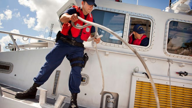 U.S. Coast Guard boatswain's mate Troy Morgan unties the boat before going out on patrol as coxswain Dalton Smith looks out of the cabin window September 16, 2014 at Station Port Huron.