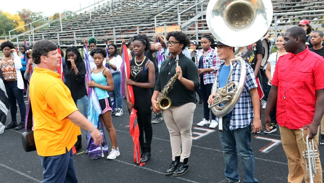 Newly returned band director Michael Smith talks with members of the East Ramapo marching band at Spring Valley High School Sept. 29, 2014. They were on the football field in front of bleachers that have been closed off until repairs can be made.