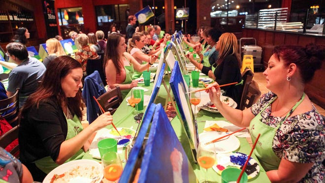 Artist Lisa Berger leads a group of budding artists as they gather at Bertucci's for Paint Nite, Tuesday, Oct. 14, 2014.