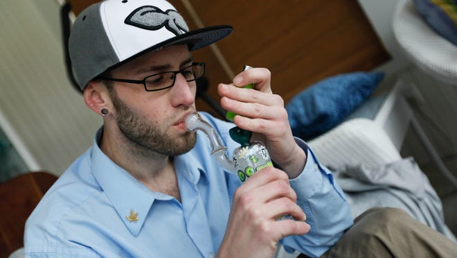 Todd Kitchen smokes marijuana in the sunroom of his Pike Creek home. Kitchen first received his medical marijuana card in 2011, but is still waiting for the state to open it's dispensary.
