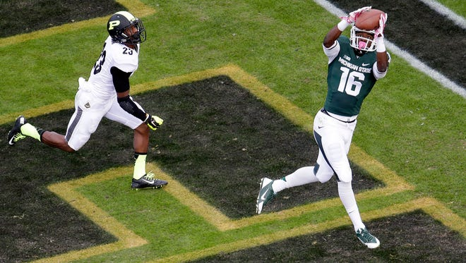 Michigan State wide receiver Aaron Burbridge (16) pulls in a 13-yard touch down pass in front of Purdue running back Keyante Green (23) in the third quarter of an NCAA college football game in West Lafayette, Ind., Saturday, Oct. 11, 2014. Michigan State won 45-31.