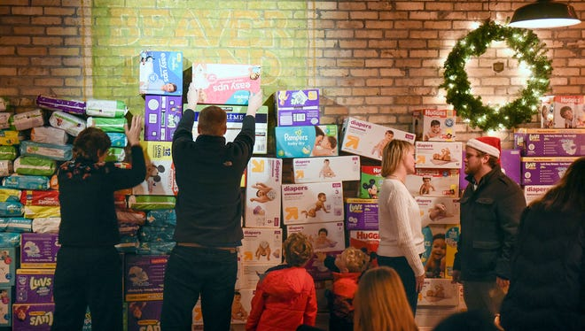 Donated diapers are piled along the walls Wednesday, Dec. 21, during an Operation Baby New Year event at Beaver Island Brewing Co. in St. Cloud.