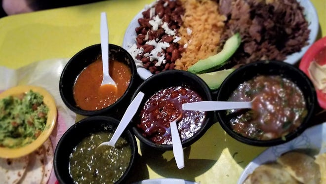 An amazing meal at Medina's. Clockwise from left. Tortillas with guacamole, four salsas, carnitas platter, crema, papas con queso, and sopes. In the center, Medina's four housemade salsas.