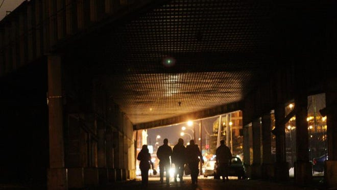 Volunteers and workers walk under the elevated train tracks near the train station in Wilmington while searching fpr homeless people as they conduct a census of homeless population throughout Delaware on Tuesday.