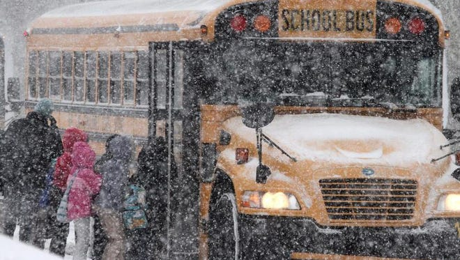 Students leave Warner Elementary in Wilmington during a Jan. 21 snow storm. Two districts have extended their school days to make up for time lost during this winter weather season to meet the state requirements for hours of instruction.