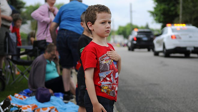 A young spectator holds his hand over his heart as the color guard passes at the beginning of the Family Fun Fest Superhero Grand Day Parade on Saturday in Waite Park.