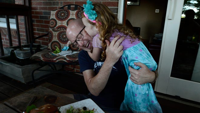 Maggie Montgomery, 4, jumps on her dad, Mark Montgomery, and gives him a kiss while eating dinner at their home Tuesday, June 7, 2016, in Pegram, Tenn. Joanna Montgomery, Mark's wife, died from cancer at the age of 47.