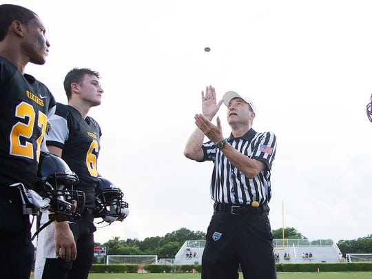 John Mantica, center, leads the coin toss between Bishop Verot High School and Estero on Thursday at Bishop Verot in south Fort Myers.