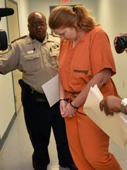 Bridget Dillon is escorted Tuesday from the Pike County Courthouse in McComb. She is accused in the slaying of Cort Gatlin, 29. The body of Gatlin was recovered Thursday in Pike County just south of Alford's Bridge. The Pike County Sheriff's Department also has charged Anthony Dauden.