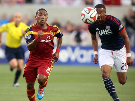Real Salt Lake forward Joao Plata (8) and New England Revolution defender Darrius Barnes (25) chase after a loose ball in the first half of an MLS soccer match, Friday, July 4, 2014, in Sandy, Utah. Real Salt Lake won 2-1.(AP Photo/Kim Raff)