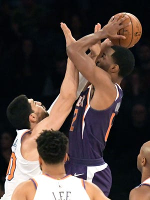 New York Knicks center Enes Kanter, left, gets a hand in the face of Phoenix Suns forward TJ Warren (12) during the first quarter of an NBA basketball game Friday, Nov. 3, 2017, at Madison Square Garden in New York. (AP Photo/Bill Kostroun)
