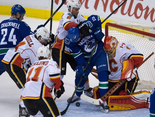 Vancouver Canucks' Derek Dorsett, center, is stopped by Calgary Flames' goalie Jonas Hiller, right, of Switzerland, while being checked by Dennis Wideman (6) as Kris Russell, second left, Mikael Backlund (11), of Sweden, and Canucks' Adam Cracknell (24) watch during the second period of an NHL hockey game in Vancouver, British Columbia, Saturday, Oct. 10, 2015. (Darryl Dyck/The Canadian Press via AP) MANDATORY CREDIT