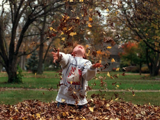 Hip, hip, hooray — fall is here! Albe Stamper, 9, revels in a pile of fallen leaves.