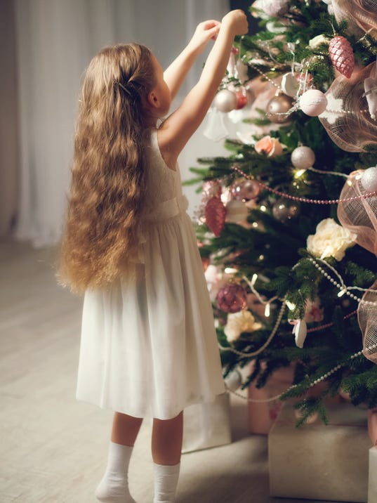 Little girl with long hair decorating christmas tree, vintage toned