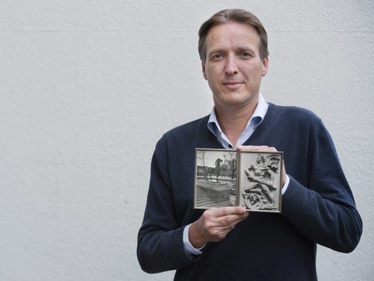 Dutch historian Arthur Brand poses with photos of sculptures