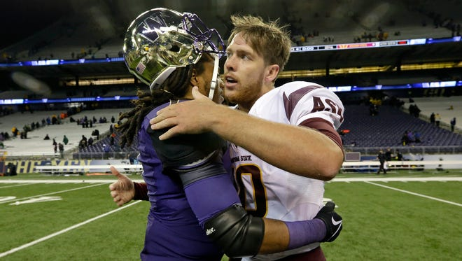 Arizona State quarterback Taylor Kelly (right) embraces Washington's Shaq Thompson after their game Saturday night at Husky Stadium in Seattle.