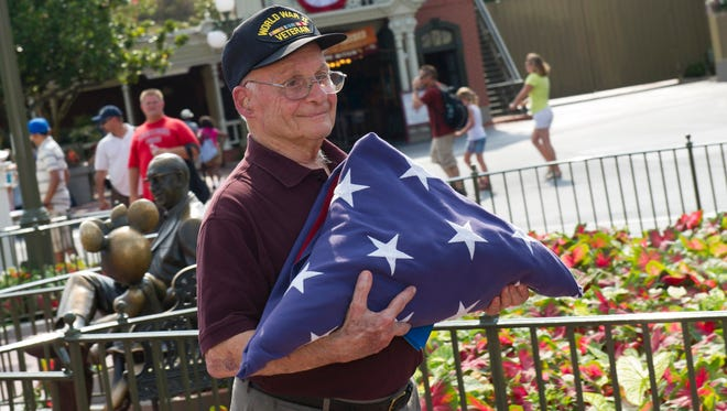 Louis Lessure, 93, a First Lieutenant bombardier from the Army Air Force and Purple Heart recipient, assists cast members in lowering the flag during the daily flag retreat at Magic Kingdom Park on his 61st wedding anniversary on July 4, 2012.