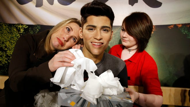 LONDON, UNITED KINGDOM - MARCH 31: A Madame Tussauds tissue attendant hands One Direction fan Laura Tokely a tissue following the news of the departure of Zayn Malik from One Direction on March 31, 2015 in London, England. (Photo by Alex Huckle/Getty Images) ORG XMIT: 545621773 ORIG FILE ID: 468191672