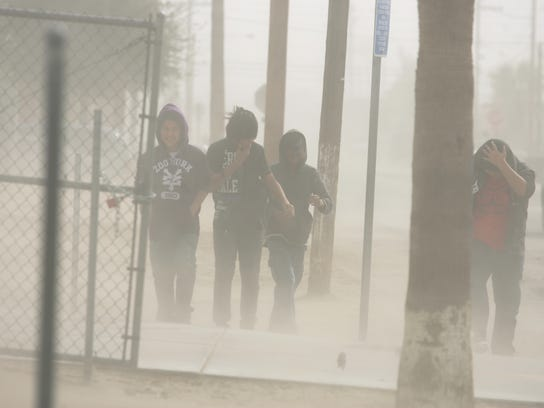 Children walk through blowing dust in Mecca, in the