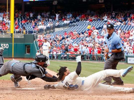 Arizona Diamondbacks catcher Chris Herrmann, left, tags out Philadelphia Phillies' Freddy Galvis, center, as he tried to score in the sixth inning of a baseball game, Sunday, June 18, 2017, in Philadelphia. The Diamondbacks won 5-4 in 10 innings. (AP Photo/Chris Szagola)