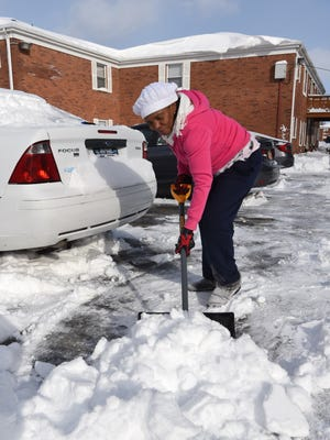 Jennifer Chevers of the City of Poughkeepsie digs out her elderly neighbor's car at Ridgefield Apartments on Jackman Drive.