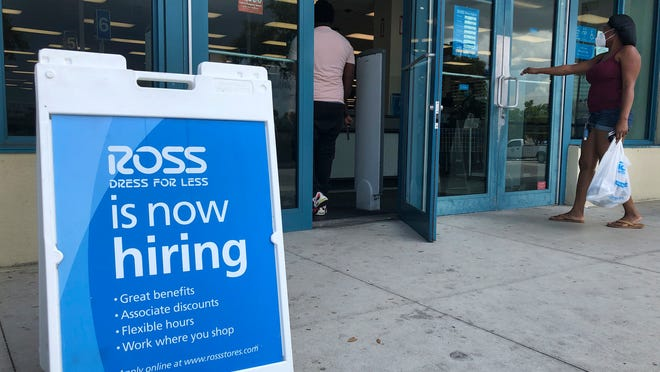 """FILE - In this July 8, 2020, file photo, a """"Now Hiring"""" sign sits outside a Ross Dress for Less store, in North Miami Beach, Fla. The United States added 1.8 million jobs in July, a pullback from the gains of May and June and evidence that the resurgent coronavirus has weakened hiring and the economic rebound."""